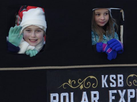 Kennebec Savings Bank featured children on its Polar Express train in Winthrop's Holiday Parade Dec. 1. Two KSB employee's children -- Lydia Garofalo, left, and Claire Cooley -- watch the crowd. (Bill Van Tassel photo)
