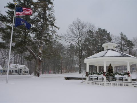 A white gazebo decorated with a lit Christmas tree, and a flagole with an American and navy blue Maine flag flying in the wind as a snowstorm rages with large pine trees in the background.